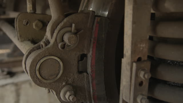 vídeos de stock, filmes e b-roll de close-up of a bogie of a train as brake pads are applied to wheels during a safety test at a repair workshop, india [with audio]. - transporte ferroviário
