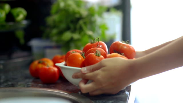 close-up of a bowl with tomatoes and hands appearing and taking the bowl - kitchen worktop stock videos & royalty-free footage