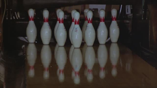 vídeos de stock, filmes e b-roll de close-up of a bowling ball striking all ten pins in a bowling alley. - cancha de jogo de boliche