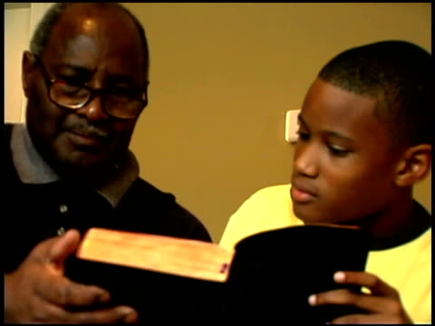 vidéos et rushes de close-up of a boy and his grandfather reading the bible together. - bible
