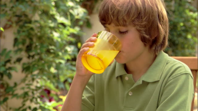 close-up of a boy drinking lemonade and eating cookies. - traditional lemonade stock videos & royalty-free footage