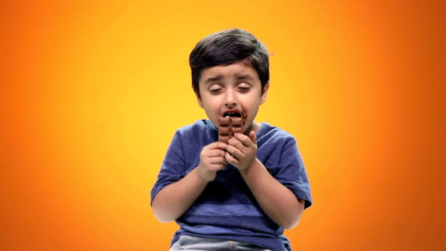 Close-up of a boy eating chocolate
