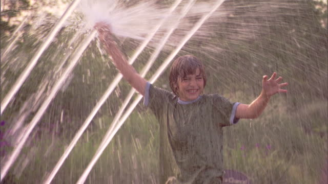 Close-up of a boy getting wet and spraying water in an arcing water fountain.