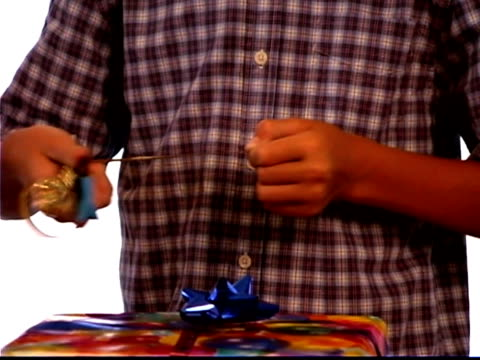 close-up of a boy using scissors to curl some ribbon for a present he is wrapping. - one teenage boy only stock videos & royalty-free footage