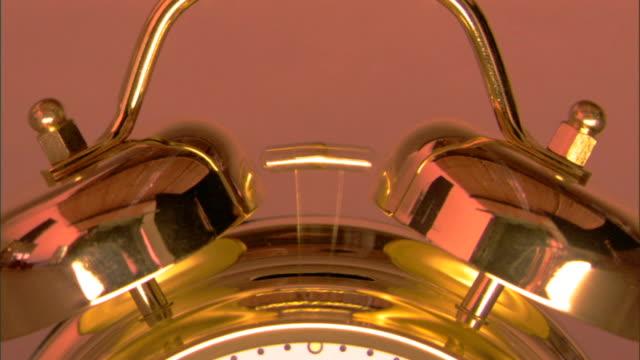 close-up of a brass alarm clock hammer ringing the bells. - 真鋳点の映像素材/bロール