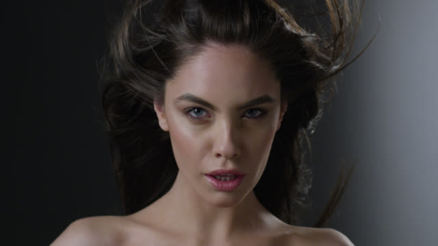 Close-up of a brunette fashion model`s face. Wind is blowing her hair. Fashion video.