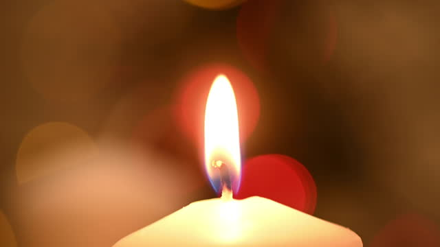 close-up of a burning candle with colourful lights in the background. - kerzenschein stock-videos und b-roll-filmmaterial
