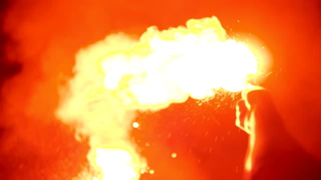 Close-up van een brandende signaal flakkering gehouden door een man