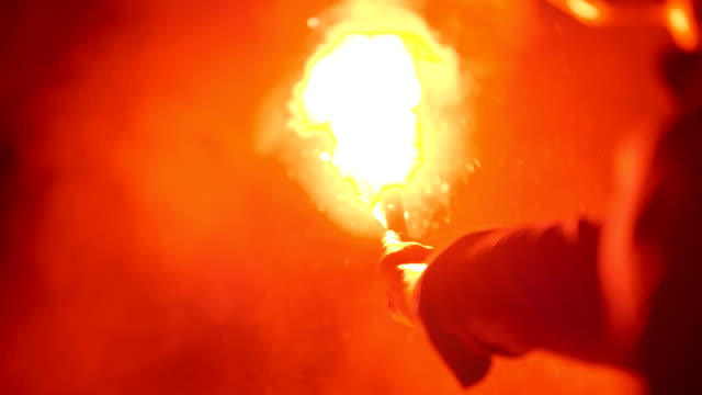 Close-up of a burning signal flare held by a man
