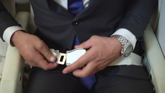 close-up of a businessman fastening the seat belt in flight - seat belt stock videos & royalty-free footage