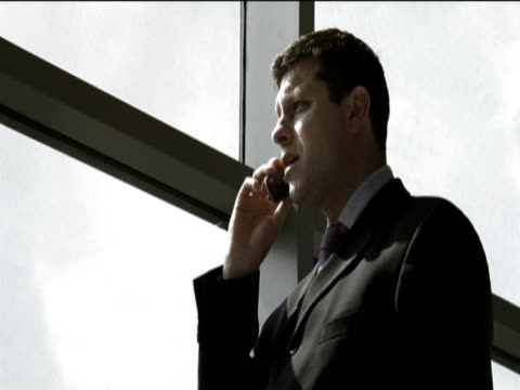 close-up of a businessman standing by a window talking on his mobile phone - kompletter anzug stock-videos und b-roll-filmmaterial