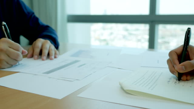 Close-up of a businessman writing a document