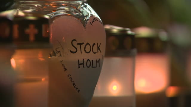 vidéos et rushes de closeup of a candlelit lantern with 'stockholm' written on it at a vigil for victims of the stockholm lorry terror attack - ambiance format raw