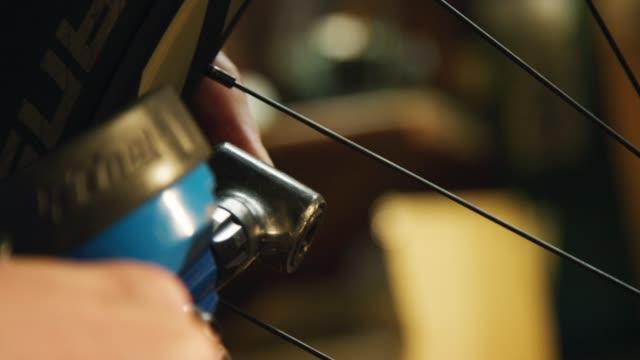vídeos de stock, filmes e b-roll de close-up de mãos de um técnico caucasiano da bicicleta do macho que desparafusa o tampão de uma válvula de pneu do shrader da bicicleta de montanha e do ar de bombeamento no pneu usando uma bomba da bicicleta - bomba de ar