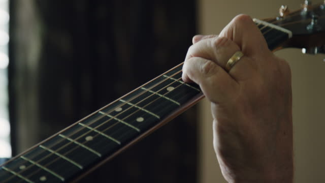 close-up of a caucasian man's fingers pressing down on the fretboard of an acoustic guitar while playing music indoors - fretboard stock videos & royalty-free footage
