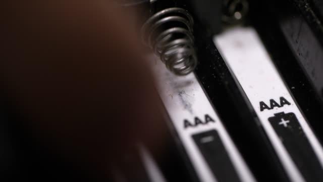vídeos de stock, filmes e b-roll de close-up das mãos de uma pessoa caucasiano que instalam baterias do triplo a (aaa) em um dispositivo eletrônico - pilha arranjo