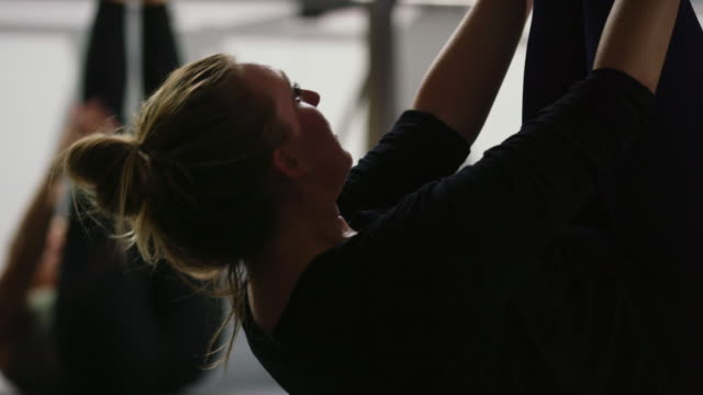 close-up of a caucasian women in her twenties leading her exercise class in pulsing pilates sit-ups with legs extended and arms outstretched in a gym - pilates stock videos & royalty-free footage