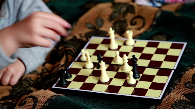 close-up of a child moving a chess piece on the the chessboard - chess piece stock videos & royalty-free footage