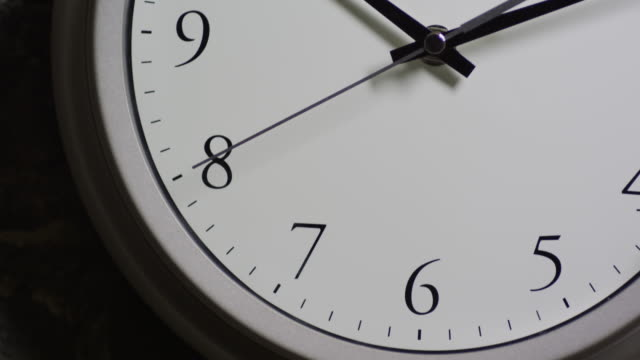 Closeup of a clock on the wall, camera tilts up as the seconds pass; 10:12.