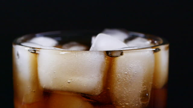 nahaufnahme eines kalten cola-glases mit eiswürfeln und blasen - cola stock-videos und b-roll-filmmaterial
