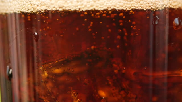 vídeos de stock e filmes b-roll de close-up of a cold cola glass with ice cubes and bubbles - gaseificado