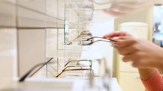 vidéos et rushes de plan rapproché d'un client ramassant des lunettes de la vitrine en magasin - tenir