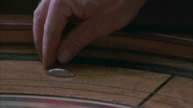 close-up of a dealer dropping a ball into a spinning roulette wheel. - roulette stock videos and b-roll footage