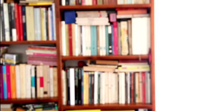 vidéos et rushes de dolly: gros plan d'une bibliothèque sans mise au point - littérature