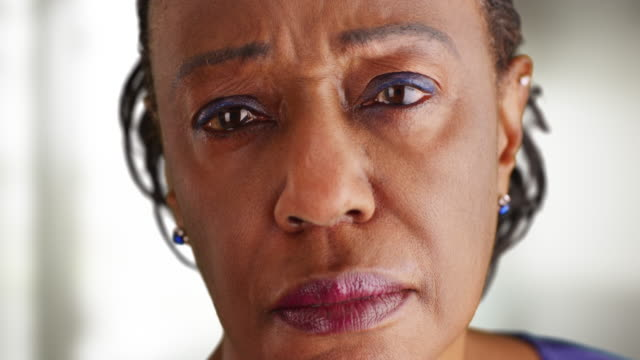a close-up of a elderly black woman looking sad - mourner stock videos and b-roll footage
