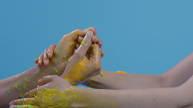 close-up of a fashion models`hands multi colored painted (yellow, orange, green, red) on blue background. fashion video. - greasepaint stock videos and b-roll footage