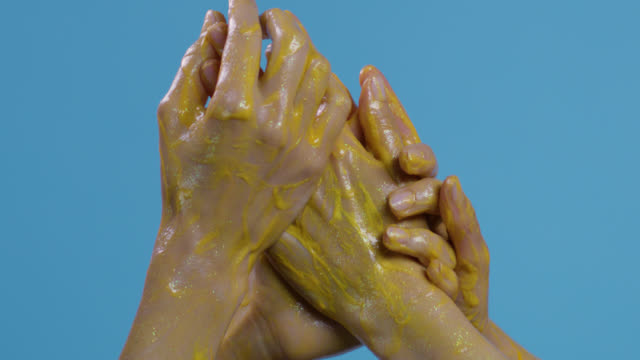 Close-up of a fashion models`hands painted yellow on blue background. Fashion video.