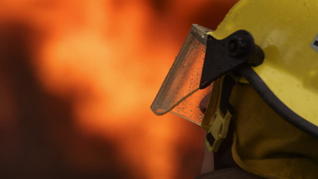 close-up of a firefighter in front of soft-focus flames - fire station stock videos & royalty-free footage