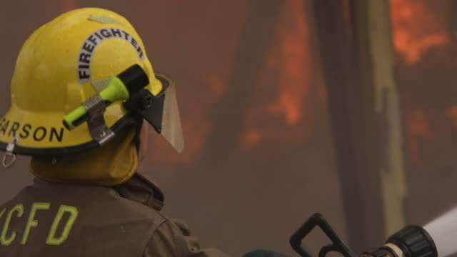 close-up of a fireman with a hose getting a tip from a co-worker - myrtle creek stock videos and b-roll footage