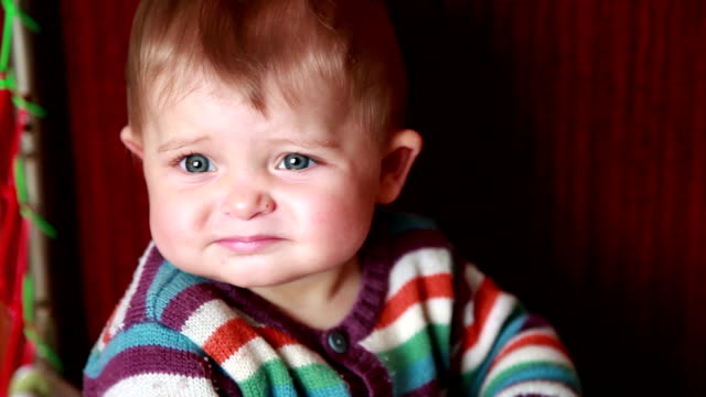 Close-up of a frowning baby sitting in the crib
