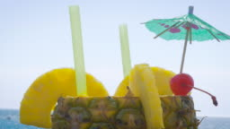 Closeup of a Fruity Cocktail Served in a Fresh Pineapple on the Beach - 4k