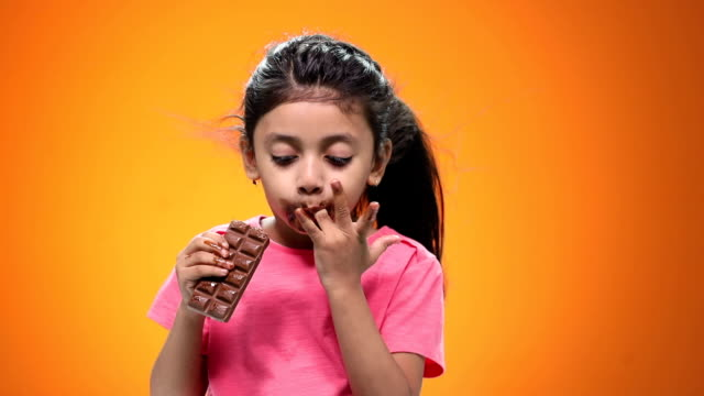 close-up of a girl eating chocolate - unhealthy eating video stock e b–roll