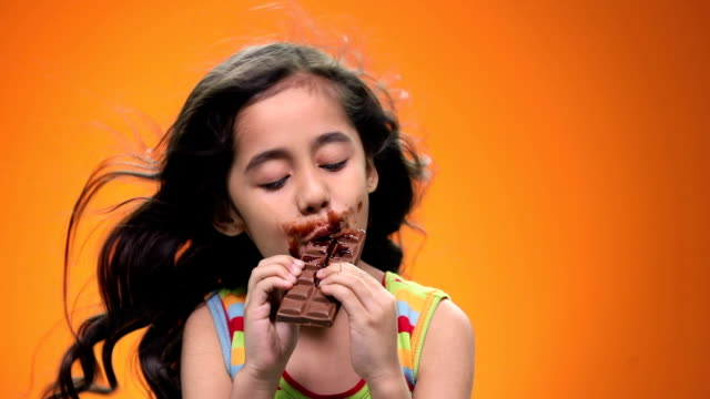 vídeos de stock, filmes e b-roll de close-up of a girl eating chocolate - fundo colorido