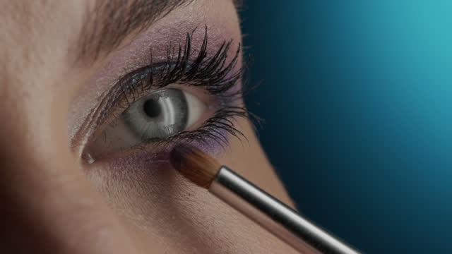 när bild av en flicka ögon som applicerar lila ögonskugga på hennes nedre lock. - smink bildbanksvideor och videomaterial från bakom kulisserna