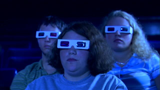 vídeos de stock, filmes e b-roll de close-up of a girl getting comfortable in her seat while watching a 3d movie. - óculos de terceira dimensão