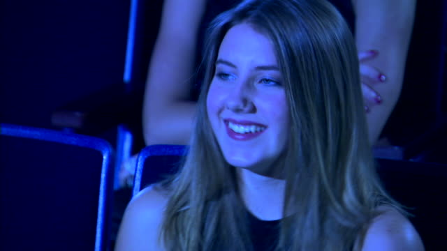 close-up of a girl laughing as she watches a movie in a dark theater. - one teenage girl only stock videos & royalty-free footage