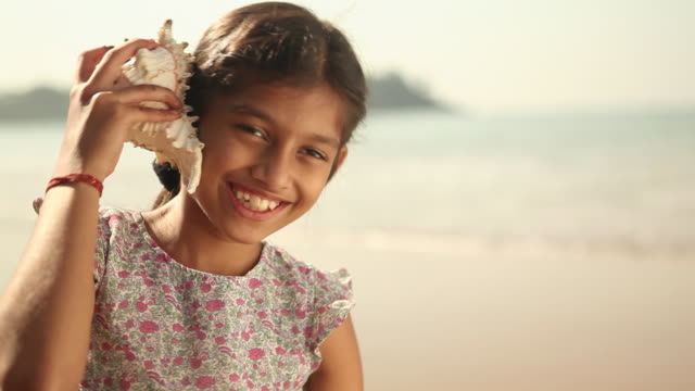 close-up of a girl listening to conch shell on the beach - conch stock videos & royalty-free footage