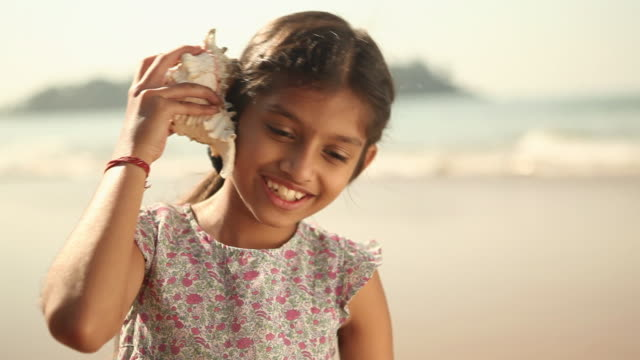 vídeos de stock, filmes e b-roll de close-up of a girl listening to conch shell on the beach - concha parte do corpo animal