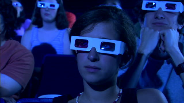 vídeos de stock, filmes e b-roll de close-up of a girl watching a 3d movie. - óculos de terceira dimensão