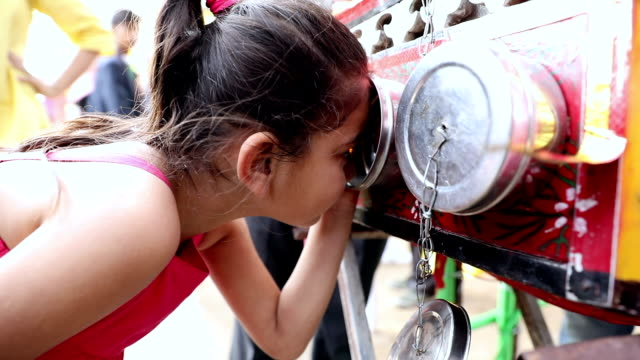 Close-up of a girl watching biscope at suraj kund fair, Haryana, India