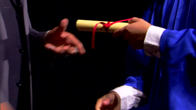 close-up of a graduates shaking hands as they receive their diplomas. - receiving stock videos and b-roll footage