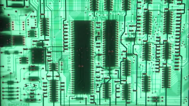 Close-up of a green circuit board that slowly racks out of focus.