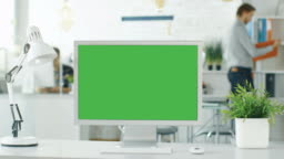 Close-up of a Green Screen on a Personal Computer. In Background Blurred and Brightly Lit Office where People go Through Office Routine.