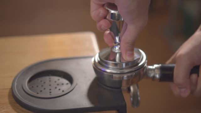 a close-up of a hand holding a portafilter with ground coffee on the edge of the table, another hand presses it with a tamper. coffee making in a bar - mar stock videos & royalty-free footage