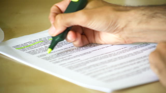 Close-up of a hand of a man completing an official form and signing it