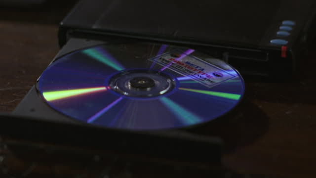 stockvideo's en b-roll-footage met close-up of a hand pushing a dvd into a player. - dvd